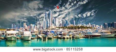 quay with yachts and skyscrapers in Abu Dhab against blue sky