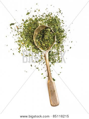dried parsley in a spoon isolated on a white background