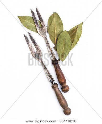 steel fork and bay leaves isolated on white background