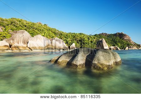Beautifully shaped granite boulders reflecting in the water at Anse Source d'Argent beach, La Digue island, Seychelles. Daytime long exposure
