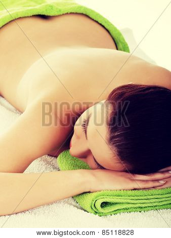 Woman lying on a massage table and is being massaged.