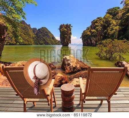 Exotic rest in Thailand. Two convenient chaise lounges and an elegant hat on one. The coast of the gulf in the Andaman Sea