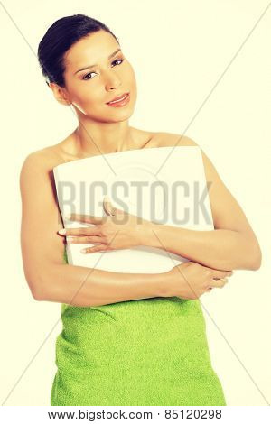 Happy fitness woman holding a scale.