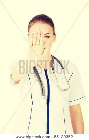 Beautiful female doctor give you reject gesture.