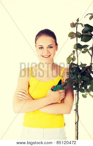 Happy gardener woman using pruning scissors.