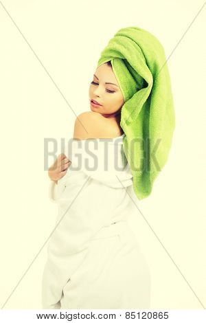 Beautiful woman in white bathrobe and towel on head.
