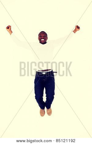 Celebration jump of african man with arms up.