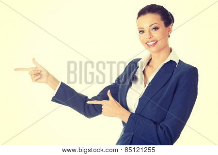 Happy attractive businesswoman pointing her finger.
