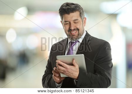 Mature businessman holding an electronic tablet inside an office building