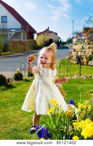Little Girl on an Easter Egg hunt on a meadow in spring, she has found an Easter egg and holding it up