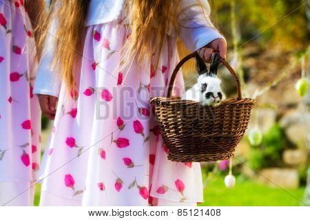 Children on Easter egg hunt in the spring on a meadow, an Easter bunny is sitting in a basket