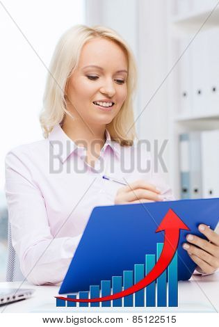 education, business and people concept - happy businesswoman or student with clipboard and growing graph writing and taking notes in office