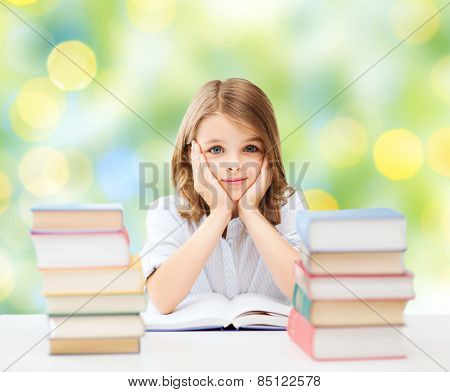 education, people, children and school concept - little student girl sitting at table with books over green lights background