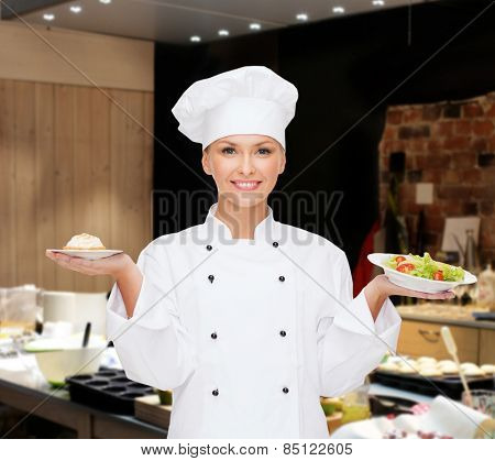 cooking, people and food concept - smiling female chef, cook or baker with salad and cake on plates over restaurant kitchen background