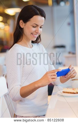drinks, food, people, technology and lifestyle concept - smiling young woman taking picture with smartphone and drinking coffee at cafe