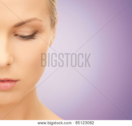 people and beauty concept - close up of beautiful young woman half face looking down over violet background