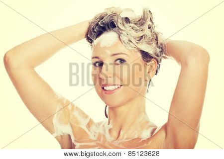 Woman taking a shower and shampooing her hair.