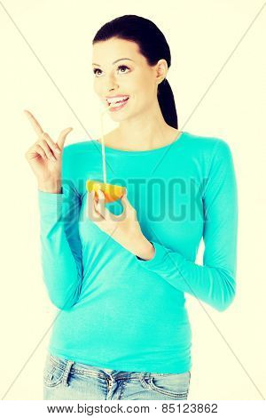 Beautiful woman drinking juice from orange with straw.