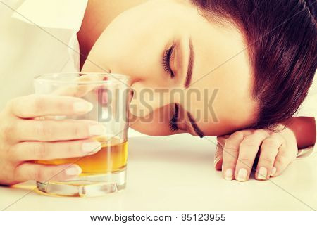 Depressed businesswoman in depression drinking alcohol.