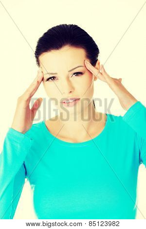 Young woman with a headache holding head.