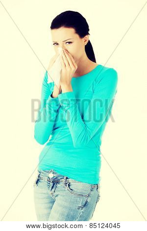 Attractive brunette woman sneezing in a tissue.