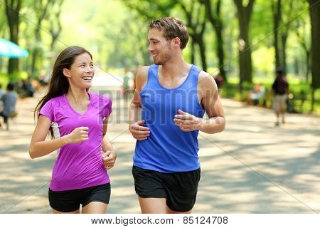 Running couple training in Central Park, New York City (NYC). Happy runners talking together during run on famous Mall walk path under trees in Manhattan, urban fitness.