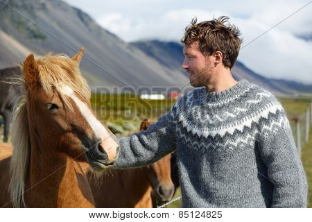 Icelandic horses - man petting horse on Iceland. Man in Icelandic sweater going horseback riding smiling happy with horse in beautiful nature on Iceland. Handsome Scandinavian model.