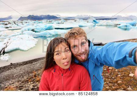Funny selfie couple taking self portrait photograph on Iceland having fun on travel by Jokulsarlon glacial lagoon / glacier lake. Tourists enjoying beautiful Icelandic nature landscape Vatnajokull.