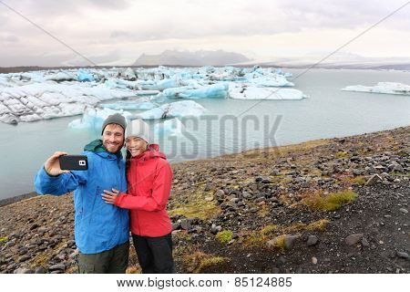 Travel couple taking selfie self portrait on Iceland photo by Jokulsarlon glacial lagoon / glacier lake. Happy tourists enjoying beautiful Icelandic nature landscape with Vatnajokull in background.