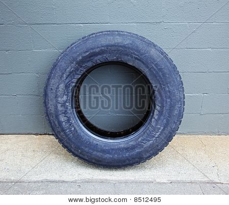 Truck Tire Leaning Aganst Building Wall