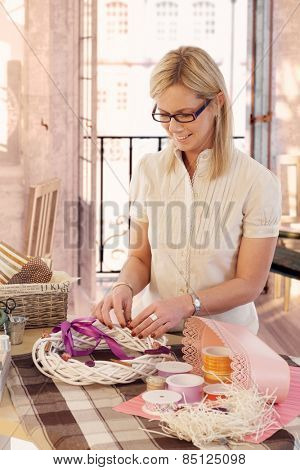 Happy casual caucasian blonde mid adult lady making valentine day wreath at home. Smiling, wearing glasses, standing at table, do it yourself, gift, present.
