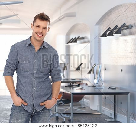 Young casual caucasian rookie businessman at creative office. Standing smiling, looking at camera, hand in pocket.