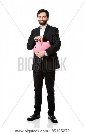 Happy handsome businessman putting a coin to piggybank.