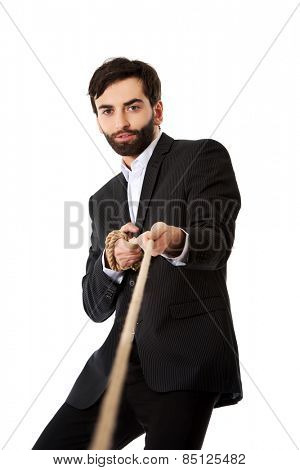 Young handsome businessman pulling a rope.