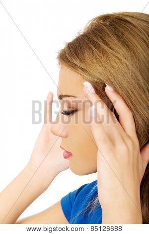 Beautiful young woman with headache touching her head.