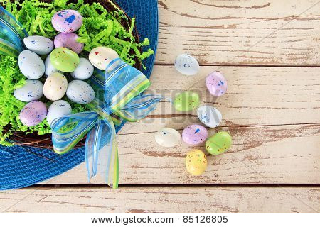 Easter eggs in a nest on a wooden table.
