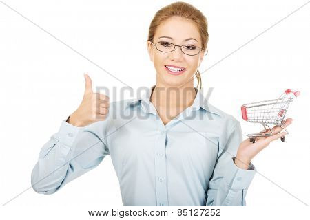 Young businesswoman with shopping cart and thumbs up.