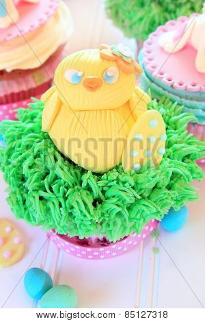 An Easter cupcake with a baby chick made out of fondant.