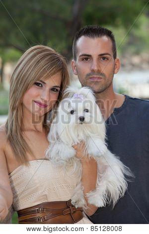 couple holding family pet dog