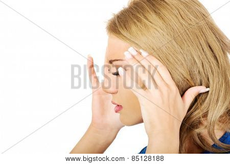 Beautiful young woman with headache touching her head.