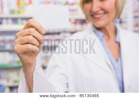 Smiling pharmacist showing calling card in the pharmacy