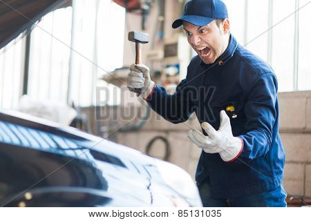 Angry mechanic smashing a car engine