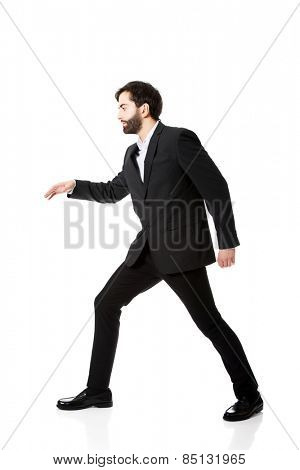 Young scared businessman walking carefully.