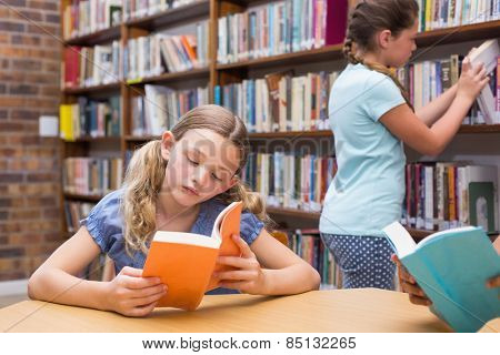 Cute pupils reading in library at the elementary school