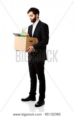 Fired businessman holding box with personal belongings.