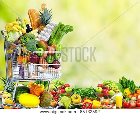 Shopping cart with vegetables over green background. Healthy diet.