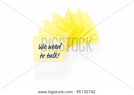 Yellow sticky note on block with message We Need To Talk