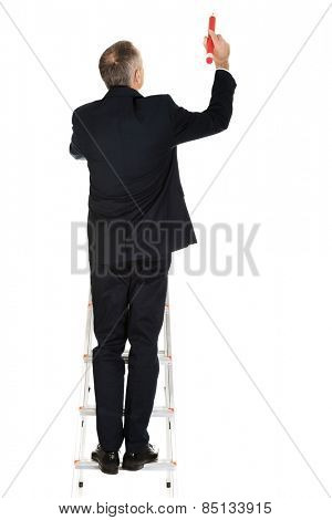 Mature businessman climbing ladder with big pencil.