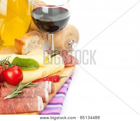 Red wine with cheese, prosciutto, bread, vegetables and spices. Isolated on white background with copy space
