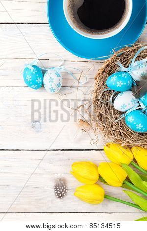 Easter background with blue and white eggs in nest, yellow tulips and coffee cup over white wood. Top view with copy space